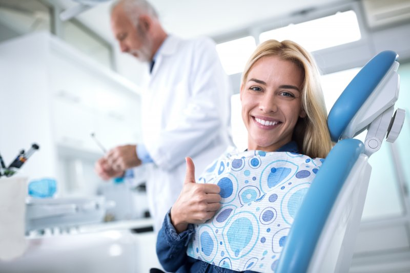 a woman smiling and giving a thumbs up in the dentist's chair