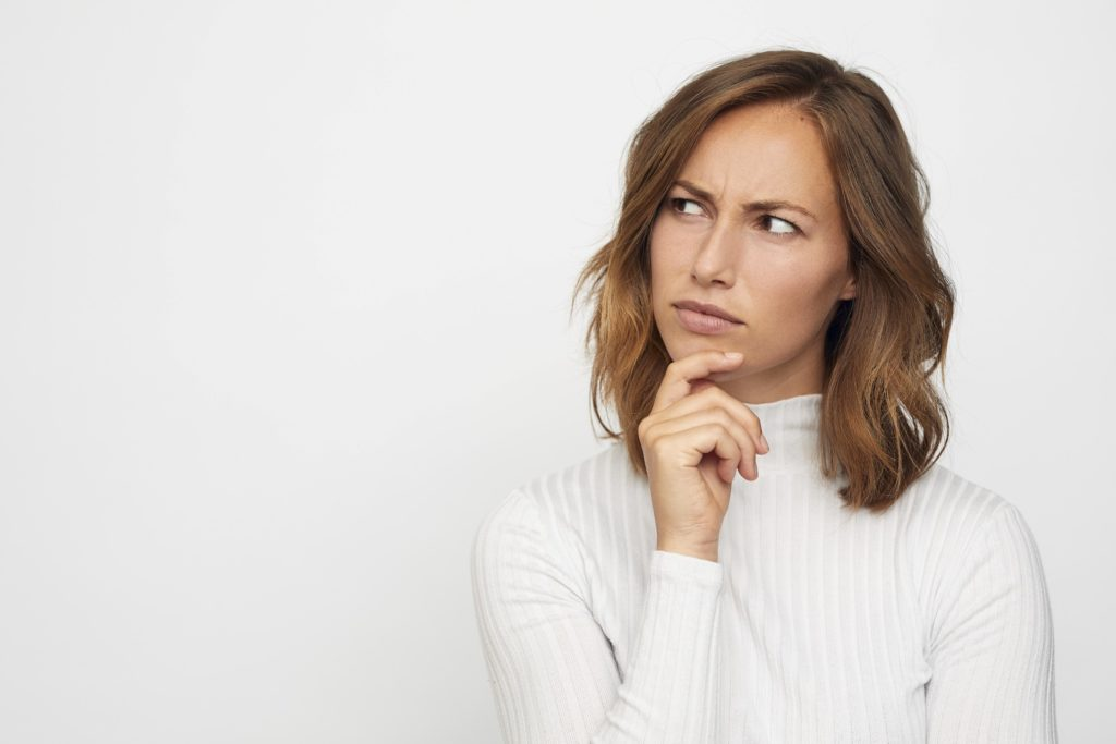 Closeup of woman in white shirt contemplating